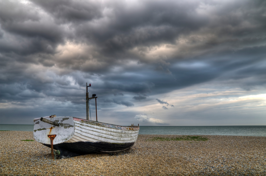 Lonely boat on beach under a stormy sky