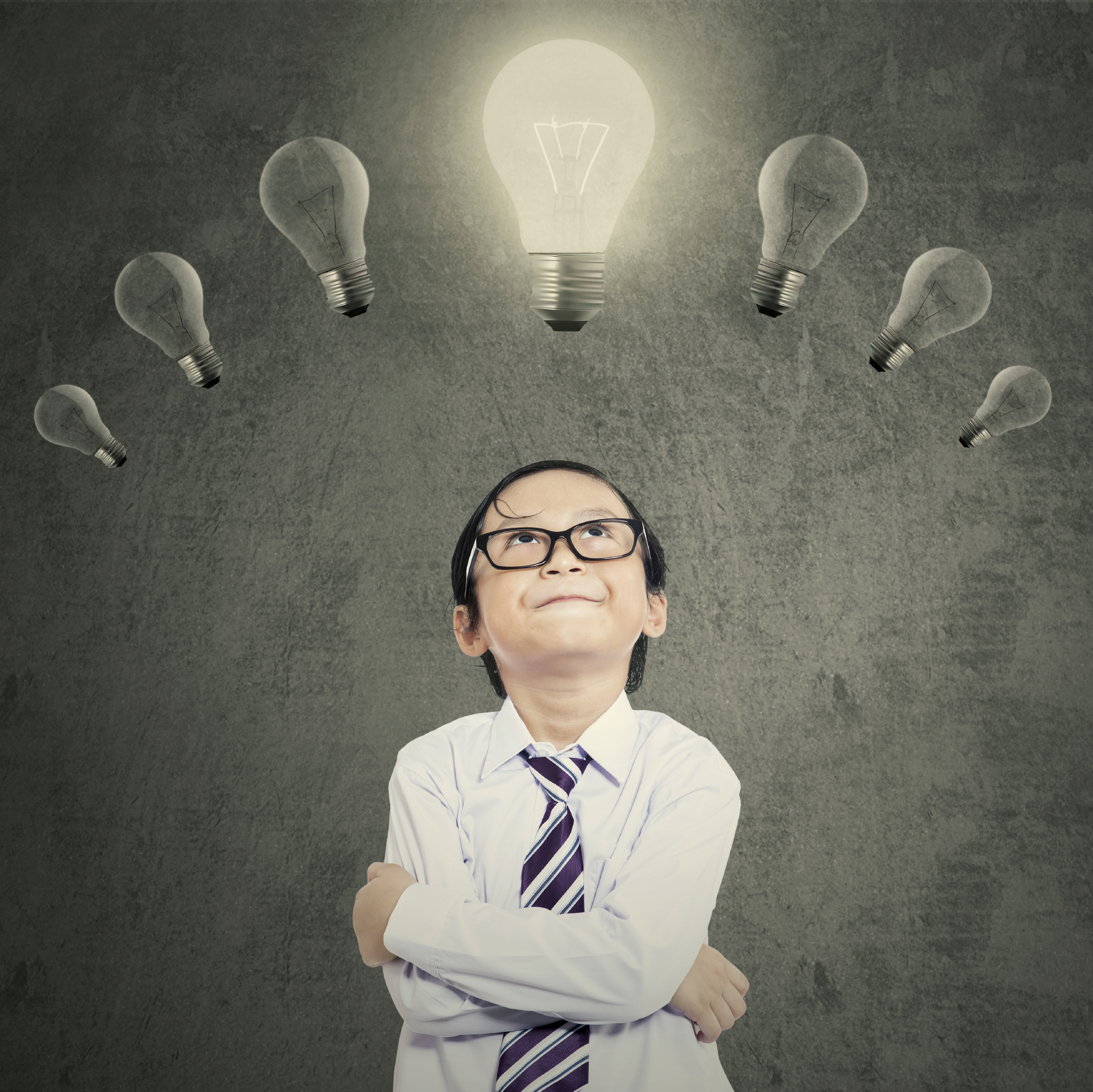 Cute little student looking at lightbulb over head, symbolizing smart student having idea