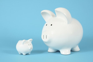 Two piggy banks, one big and one small, on a bright blue background