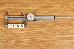 A caliper measuring the word RISK. Concept for risk management.