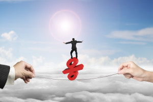 Two hands pulling rope with businessman balancing on red percentage sign, on sun sky cityscape background.