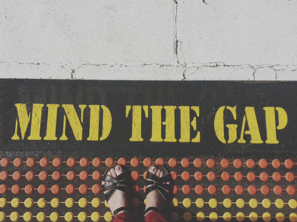 Standing by a mind the gap notice