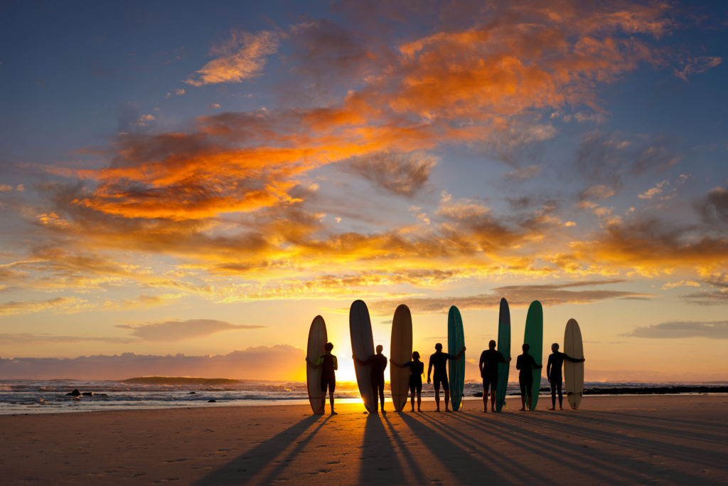 A group of young and old malibu (longboard) surfers about to go surfing at sunrise.